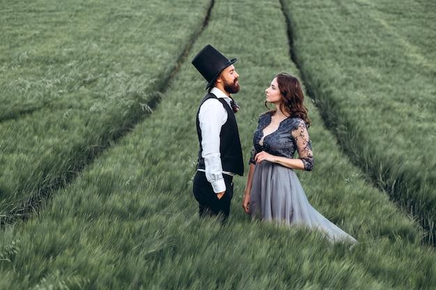 Elegant bride and groom walking and posing on green field