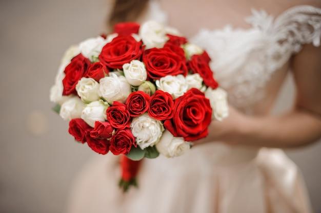 아름다운 흰색과 빨간색 장미 꽃다발을 들고 웨딩 드레스에 우아한 신부