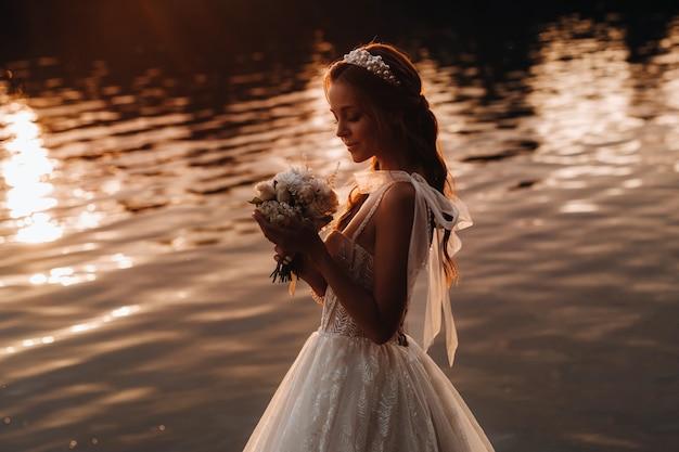 Нарядная невеста в белом платье и перчатках стоит у реки в парке с букетом