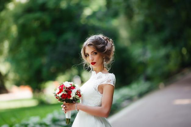 エレガントな花嫁の結婚式の日に屋外でポーズ