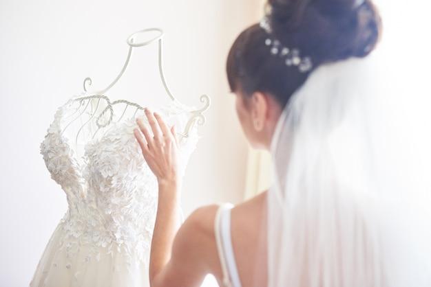 エレガントな花嫁は彼女の部屋にウェディングドレスを置きます。