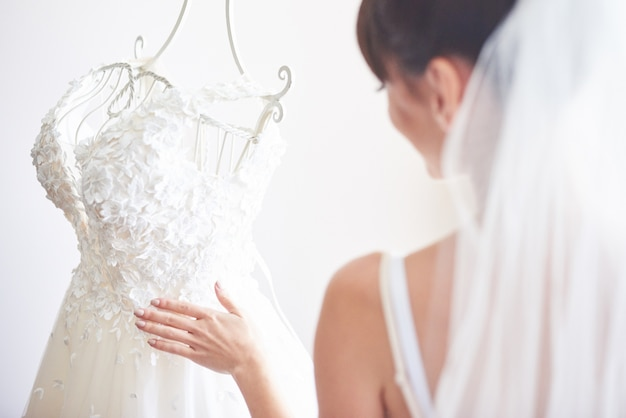Elegant bride puts a wedding gown in her room.