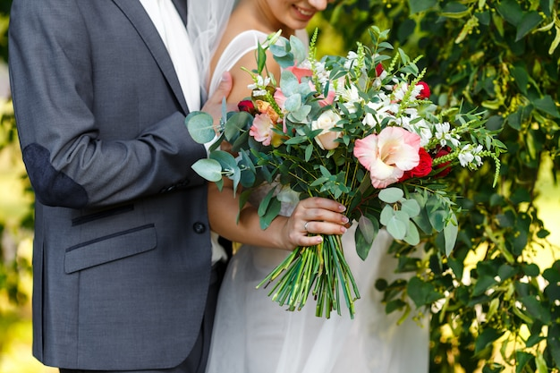 Elegant bride in a wedding dress with lace and groom in grey suit holding in hands bridal bouquet of flowers