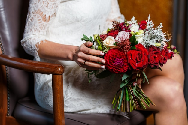 Elegant bride in a wedding dress with lace holding bridal bouquet of flowers