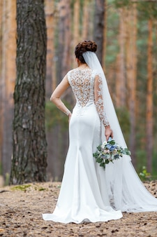 Elegant bride in a wedding dress with lace standing in the woods holding bridal bouquet of flowers