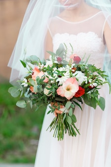 Elegant bride in a wedding dress with lace and veil holding bridal bouquet of flowers
