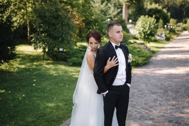 屋外を歩いて楽しんでいるハンサムなスタイリッシュな新郎とエレガントな花嫁。結婚式のカップル