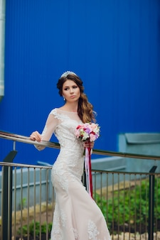 Elegant bride with wedding flowers bouquet, attractive woman in wedding dress. young girl in white dress goes the stairs of a beautiful white house. happy newlywed woman. bride with wedding makeup