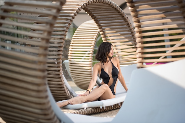 Elegant brunette female in black swimsuit with a perfect body sitting