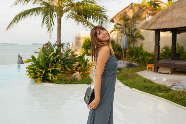 Элегантная брюнетка женщина в сексуальном платье позирует в стильном отеле в азиатском стиле.
