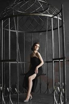 Элегантная брюнетка в черном платье и позирует в большой птичьей клетке