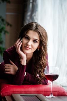 레스토랑에서 레드 와인의 유리와 함께 빨간색 이브닝 드레스에 우아한 갈색 머리 아가씨
