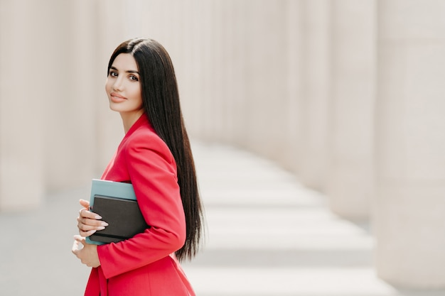 Elegant brunette lady with dark long straight hair, dressed in fashionable red suit