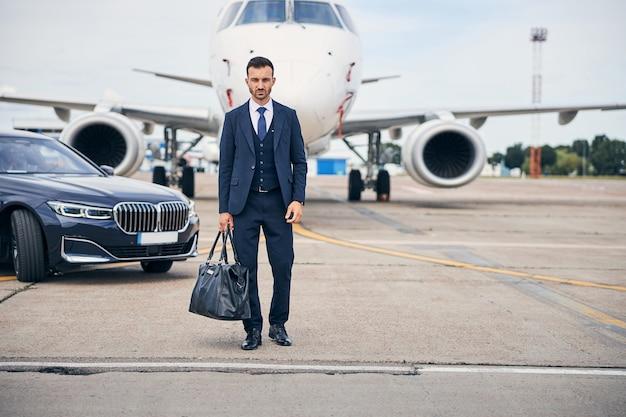航空機の前に立っている黒いバッグを保持しているスーツを着ているエレガントなブルネットの男