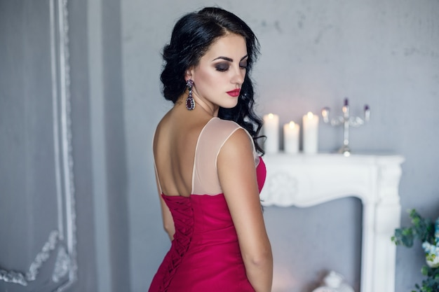 ファッショナブルなドレスでエレガントなブルネットのセクシーな女性。赤い唇のメイクで魅力的な女の子モデル