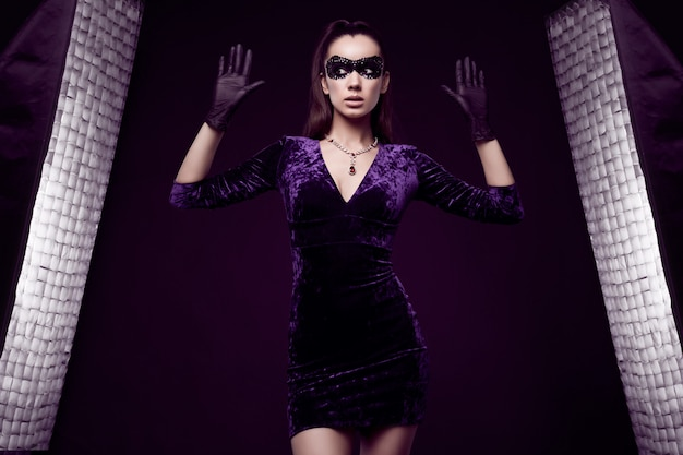 Elegant brunette woman in beautiful dress, sequins mask and gloves surrenders