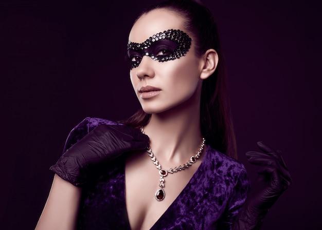 Elegant brunette woman in beautiful purple dress, sequins mask and black gloves