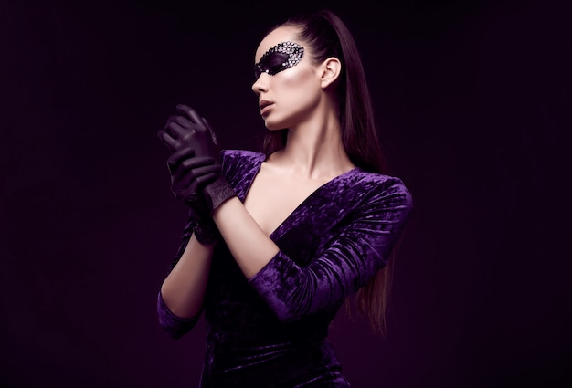 Elegant brunette woman in beautiful purple dress and sequins mask glove up