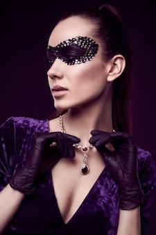 美しい紫色のドレス、スパンコールマスク、黒い手袋でエレガントなブルネットの女性