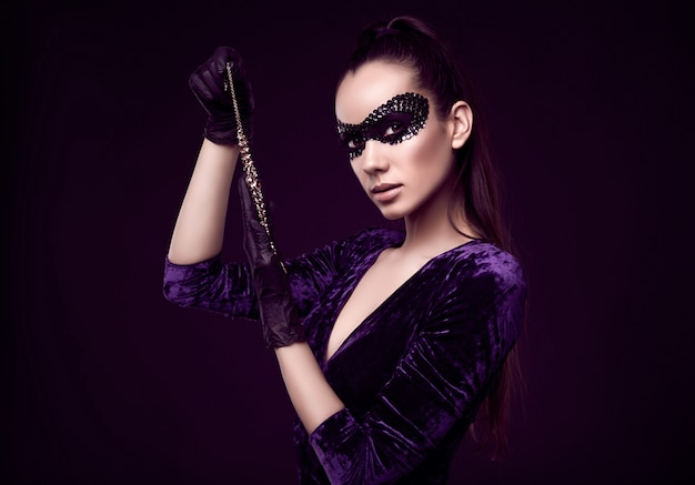 Elegant brunette woman in sequins mask with black gloves looks at diamond necklace