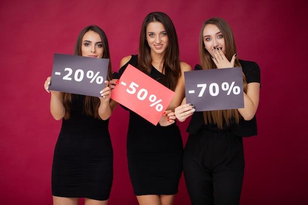 Elegant brunette women wears black dress holding shopping bags, black friday concept