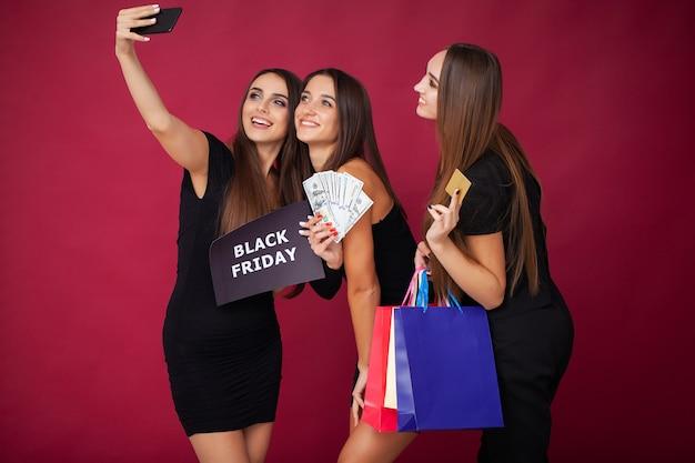 Elegant brunette women wears black dress holding shopping bags, black friday