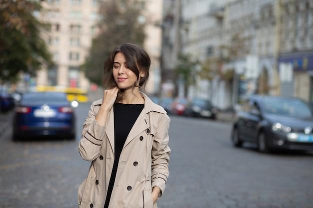 エレガントなブルネットの若い女性は、通りで流行のコートの散歩を着ています。テキスト用のスペース