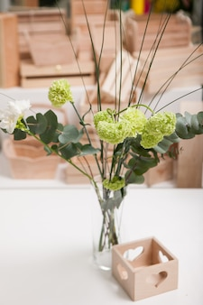 Elegant bunch of flowers in glass vase on white table, handmade wooden present box nearby floristics workshop, floral arrangement for gifts with love, st.valentines day, decoration concept