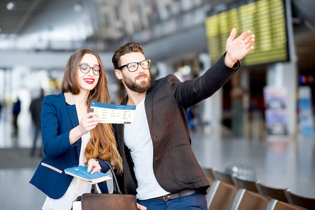 Elegant business couple standing with suitcase and airplane tickets at the waiting hall in the airport. business travel concept