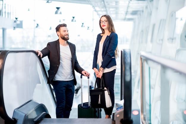 空港の出発エリアへのエスカレーターで起き上がる荷物とエレガントなビジネスカップル