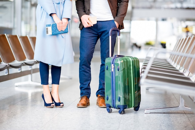 Elegant business couple with suitcase, phone and tickets standing at the airport. close up view on the legs
