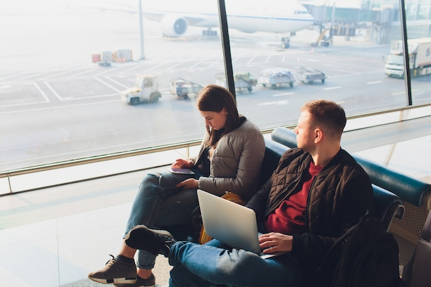Elegant business couple working with laptop and phone sitting at the waiting hall in the airport. business travel concept.