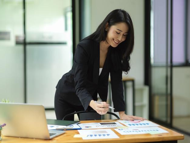 エレガントなビジネス女性が立って、オフィスの机の上でビジネス書類をチェックします