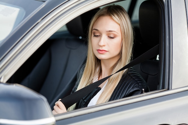 Elegant business woman dressed in the suit fastening the safe belt before driving his car