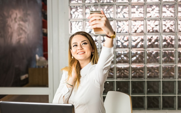 Elegant business woman making selfie with cellphone.