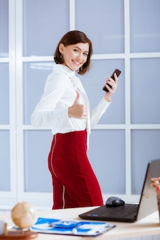 사무실에서 엄지 손가락 기호를 보여주는 우아한 비즈니스 여자.