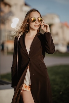 街で夏の暑い日にサングラスを着てエレガントなビジネス女性
