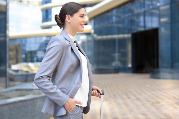 공항에 수하물이 있는 우아한 비즈니스 여성. 비즈니스 여행에 가방을 가진 사업가입니다.