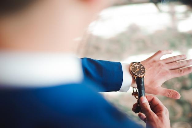 Elegant businessman dressed clock before meeting with partners.