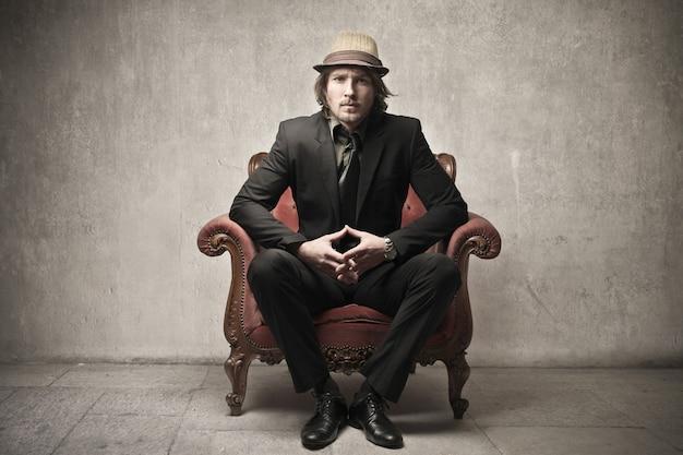 Elegant businessman sitting on an armchair
