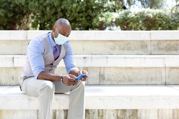 彼のスマートフォンを使用してエレガントなビジネスマン。彼は外にいて、医療用マスクを着用しています。
