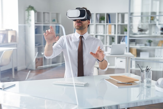 Elegant businessman in vr headset pointing at transparent computer screen while sitting by desk in office
