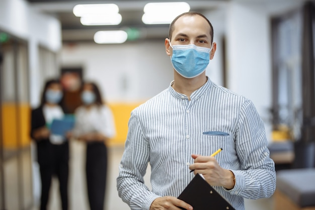 Elegant businessman wearing a medical mask stands in the office corridor with a tablet in his hands.