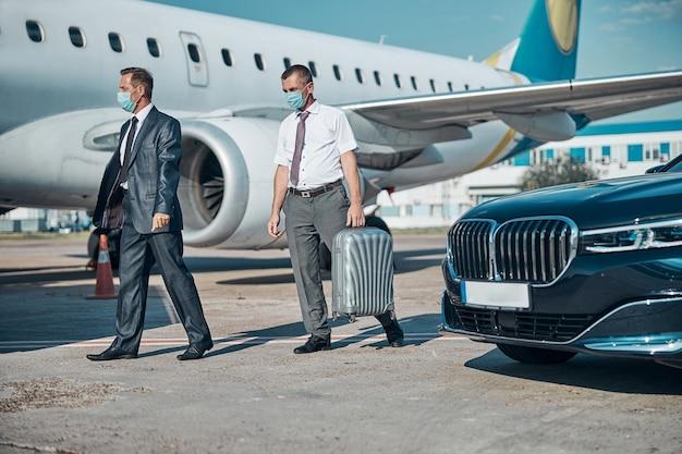 スーツケースを持ったアシスタントを持つエレガントなビジネスマンが検疫中に飛行するために空港の滑走路に車で来ています
