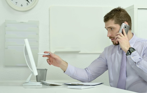 Elegant businessman with computer and phone in office