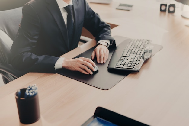 Elegant businessman works on computer in office