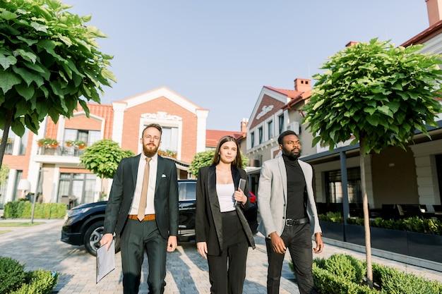 Элегантные бизнесмены, африканец и кавказец, кавказская женщина, прогулки на свежем воздухе во дворе современного офисного бизнес-центра.
