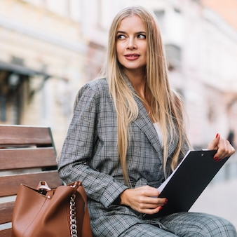 Elegant businesswoman on bench with clipboard