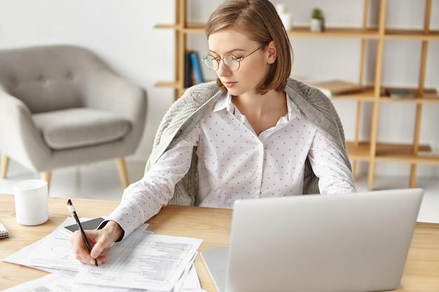 Элегантная деловая женщина, одетая официально, сидя с ноутбуком