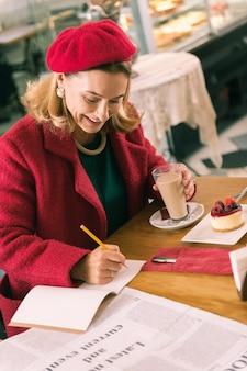 Элегантная деловая женщина. элегантная зрелая бизнес-леди делает заметки, сидя в пекарне и пьет кофе